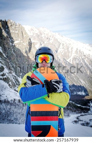 The man with the snowboard is on the background of mountains - stock photo