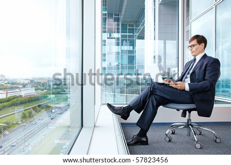 The man works for a laptop in the office with a view from the window - stock photo