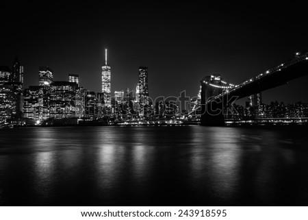 The Manhattan skyline and Brooklyn Bridge at night seen from Brooklyn Bridge Park in Brooklyn, New York. - stock photo