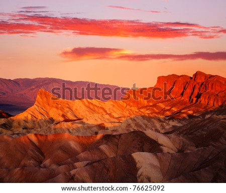 The Manley Peak Ablaze With Orange Light As If Lit From Within At First Light Of Dawn Over Zabriskie Point, Death Valley National Park, California, USA - stock photo