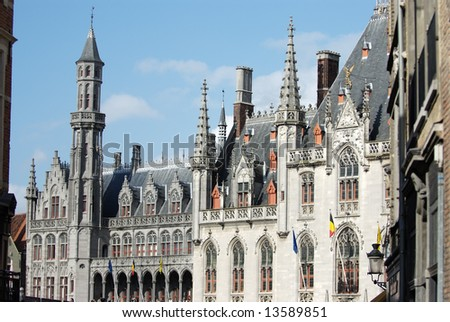 The market square in Bruges, is the medieval commercial centre of the city. The Provincial Court was rebuilt in neo-gothic style after it had been demolished. - stock photo
