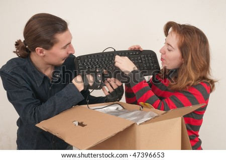 The married couple has opened a cardboard box where the computer is packed. - stock photo