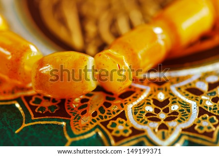 The Masbaha is also known as Tasbih is a string of prayer beads, seen here wwith the Quran as a background - stock photo