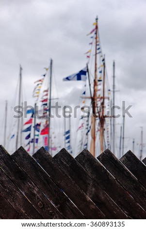 The masts of the yacht harbor painted boards of the fence on the background of clouds in the sky - stock photo