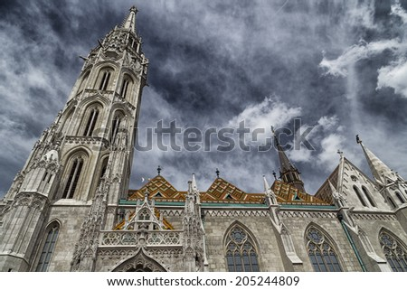 The Mathias Church in Budapest (Hungary) or Church of Our Lady: red and orange diamond patterned roof tiles, neo-Gothic windows and white towers on dark cloudy dramatic sky - stock photo