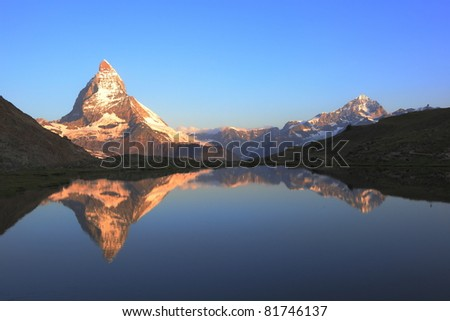 The Matterhorn peak and reflections on the Riffelsee in early morning - stock photo