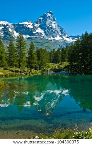 the Matterhorn reflected in the clear waters of blue lake, Valtournenche - Aosta Valley - stock photo
