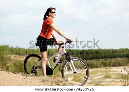 The mature beautiful woman, on bicycle, stand on  beauty nature - stock photo