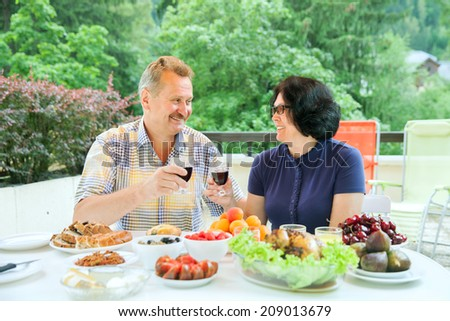 The mature couple looks at each other and clink glasses of wine