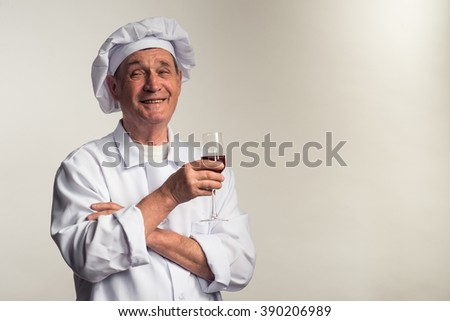 The mature man in a suit chef holding a glass of red wine, studio.