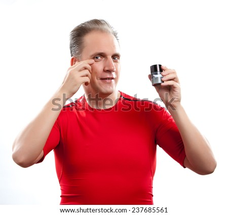 The mature well groomed man cares of the appearance - uses  against wrinkles cream   - stock photo