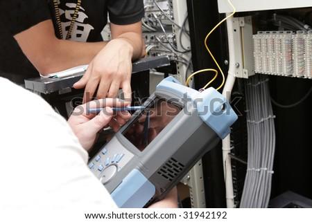 The measurement of fiber optic link on telecom site - stock photo