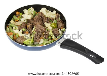 The meat (horse) with vegetables in a frypan. Isolation on a white background. Clipping path.