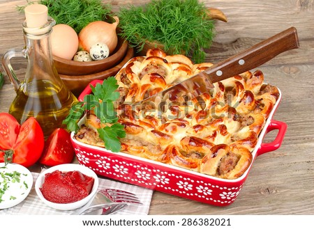 The meat pie made at home and fresh vegetables on a wooden background. - stock photo