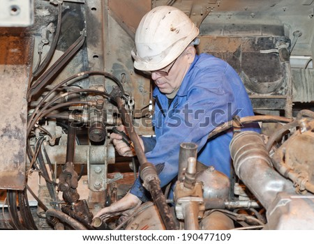 the mechanic dressed in dirty overalls serves mechanisms - stock photo