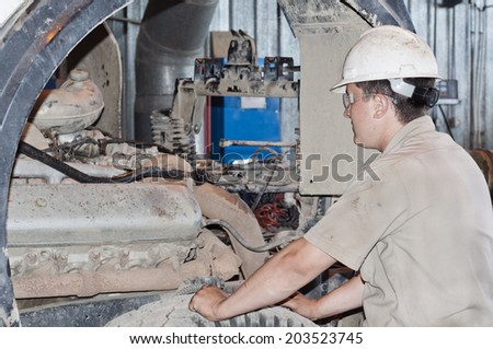 The mechanic looks at the truck engine before repair - stock photo