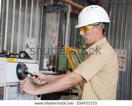the mechanic works at the lathe at factory - stock photo