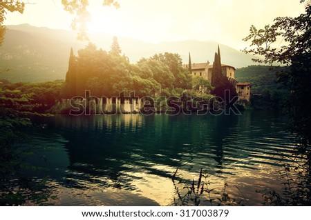 The Medieval Castle Toblino near Toblino Lake against Alpine rocks. Trentino, Italy - stock photo