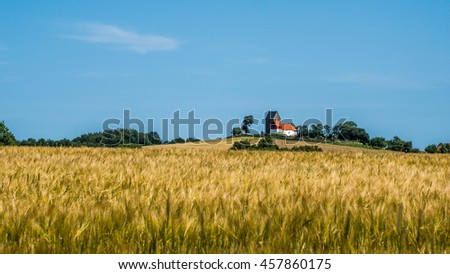 The medieval idyllic church of Rutsker sitting on a hill above a rye field on the Danish island Bornhom