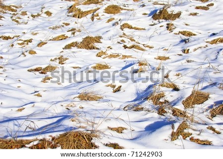 The melting snow reveals the dead grass beneath it in the field. - stock photo