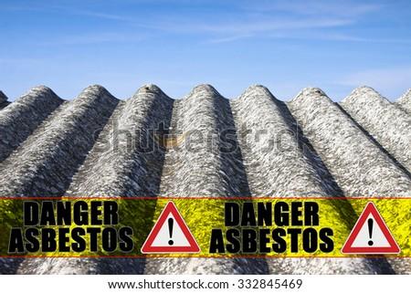 "The message ""danger asbestos"" written on a yellow stripe - stock photo"
