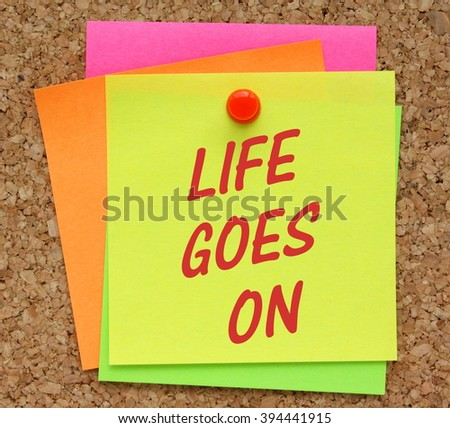The message Life Goes On in red text on a yellow sticky note pinned to a cork notice board as a reminder - stock photo