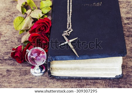 The metal  cross  over the  old bible with world globe model and  red roses on wooden background, world mission concept.  - stock photo