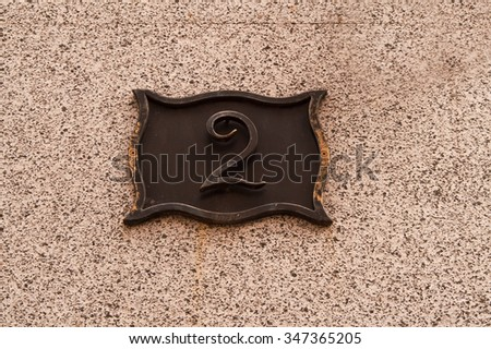 The metal plate with the house number 2 - stock photo