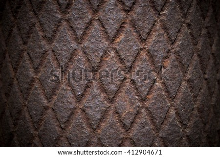 The metal sheet with a pattern of diamond shapes. Dark brown color, photo made in the grunge, gloomy. It can be used as the background or texture for any photo editor.