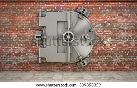 The metallic bank vault door on the brick wall. Concept of safety. - stock photo