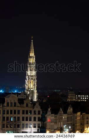 The 96 meter high belfry of Brussels townhall with a five meter high metal statue of archangel Michael patron saint of Brussels faraway photographed at night - stock photo