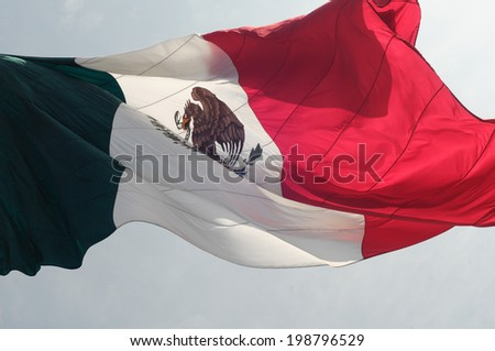 The Mexican flag flying, seen in the middle of the Zocalo square in Mexico City - stock photo