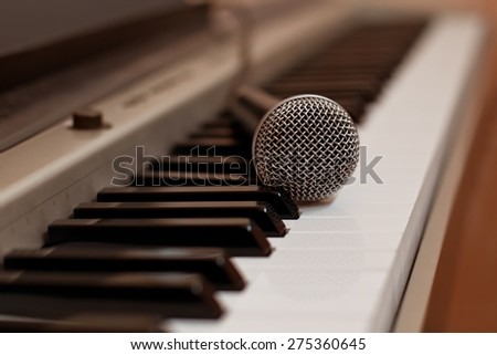 The microphone lying on the keyboard of the synthesizer in Golden tones - stock photo