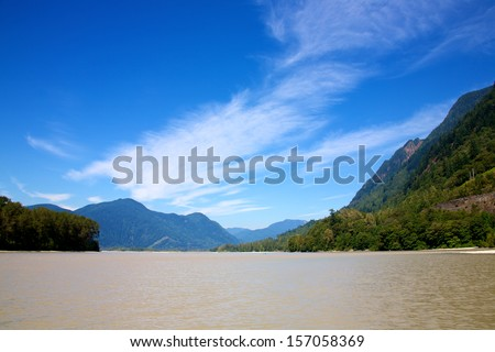 The mighty Fraser River in beautiful British Columbia Canada set against a deep blue sky - stock photo