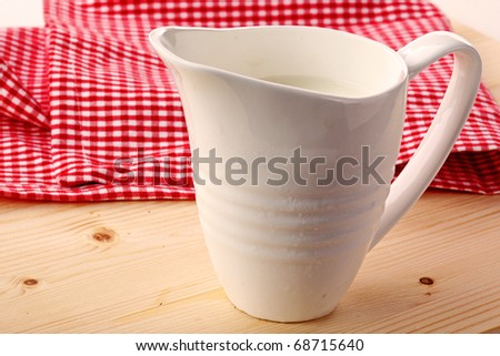 The milk in the jar isolated on wooden table
