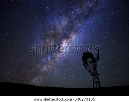 The milky way core rises above a windmill in the Karoo desert, South Africa. - stock photo