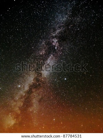The milky way galaxy over orange lights - stock photo