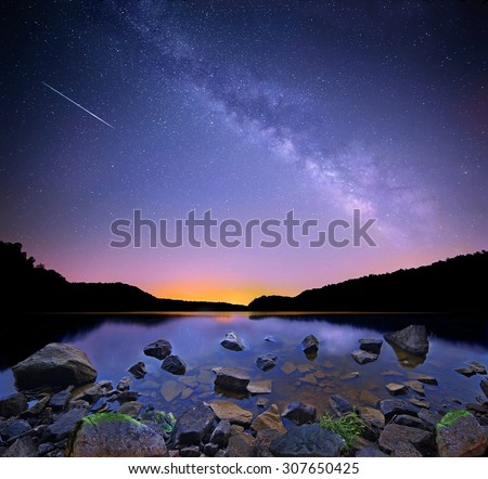 The Milky Way over Salt Fork lake, Ohio with a Perceid meteor streaking in from the northeast. - stock photo