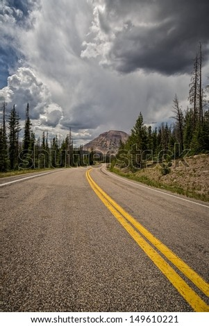 The Mirror lake highway or highway 150 that goes through the Unitas's Mountains in Utah with thunderclouds by Reids Peak/ The Road Home - stock photo
