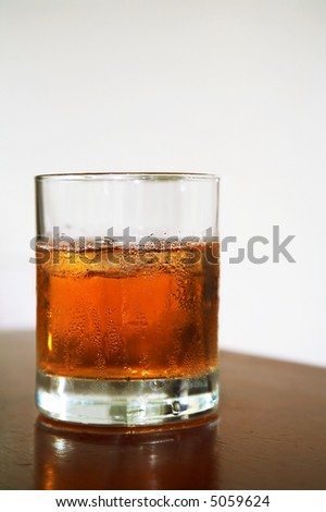 The misted over glass of whisky with an ice on a table