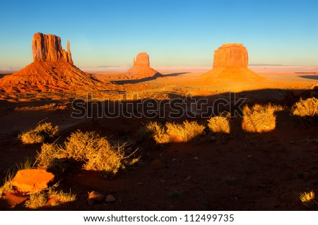 The Mittens of Monument Valley with shadows lengthening in the setting sun - stock photo