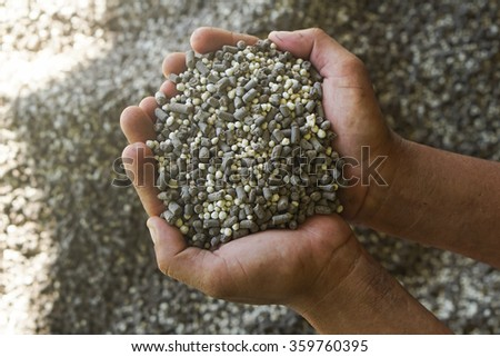 The mix of plant chemical fertilizer and manure on farmer hands. - stock photo