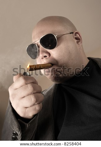 The Mobster, Boss, Head Honcho, Top Dog...  An image of the Man in charge, smoking a cigar.  Focus is on the cigar, while mobster is de-saturated for meaner look. - stock photo