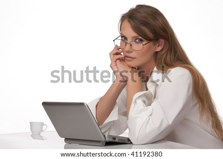 The modern, beautiful, young woman sits at a table with a personal computer