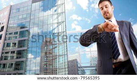 The modern businessman looking at wrist  watch on background a office building - stock photo