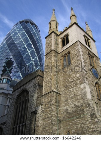 The modern glass offices of the Swiss Re Gherkin rising from behind historic stone church, City of London, England uk - stock photo