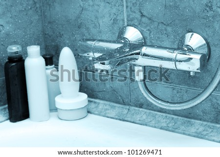 The modern tap in bathroom and shampoos at a background - stock photo