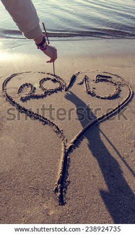 the moment of 2015 written in a heart shape at beach. will be in love in 2015 - stock photo