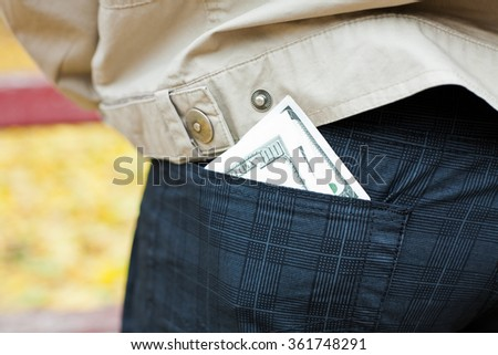 The money in the back pocket of man's trousers