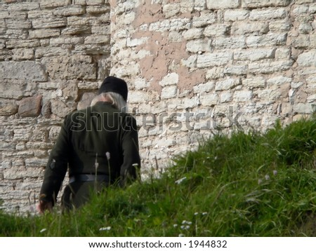The Monk in black leaves to conventual wall. - stock photo